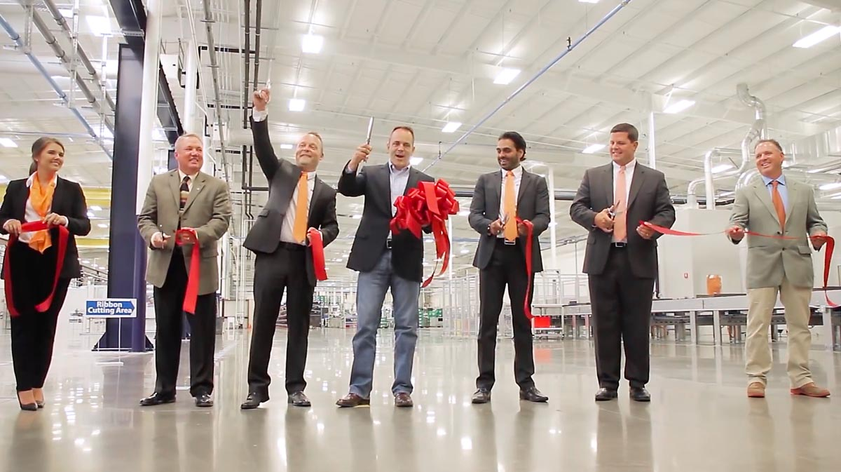 red ribbon cutting at plant opening in Russell County